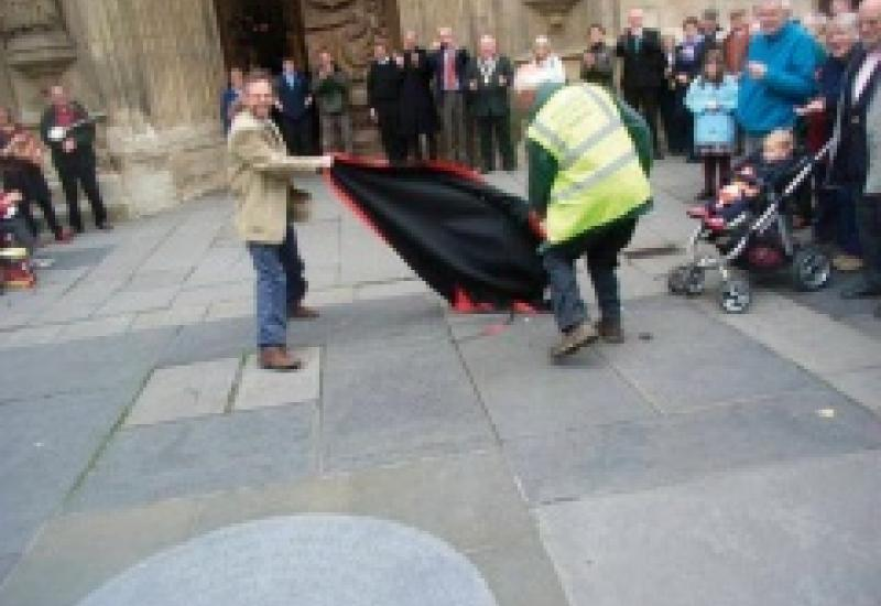 Artist Iain Cotton unveils his work in front of Bath Abbey assisted by Cotswold Voluntary Warden John Walker.